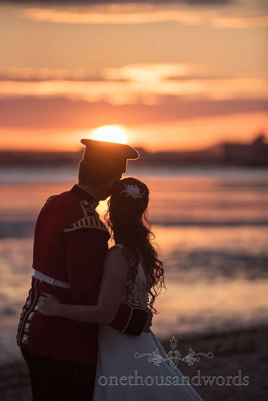 Military groom in uniform Wedding Couple hugging Watch Sunset Over the Sea on Dorset beach Photograph