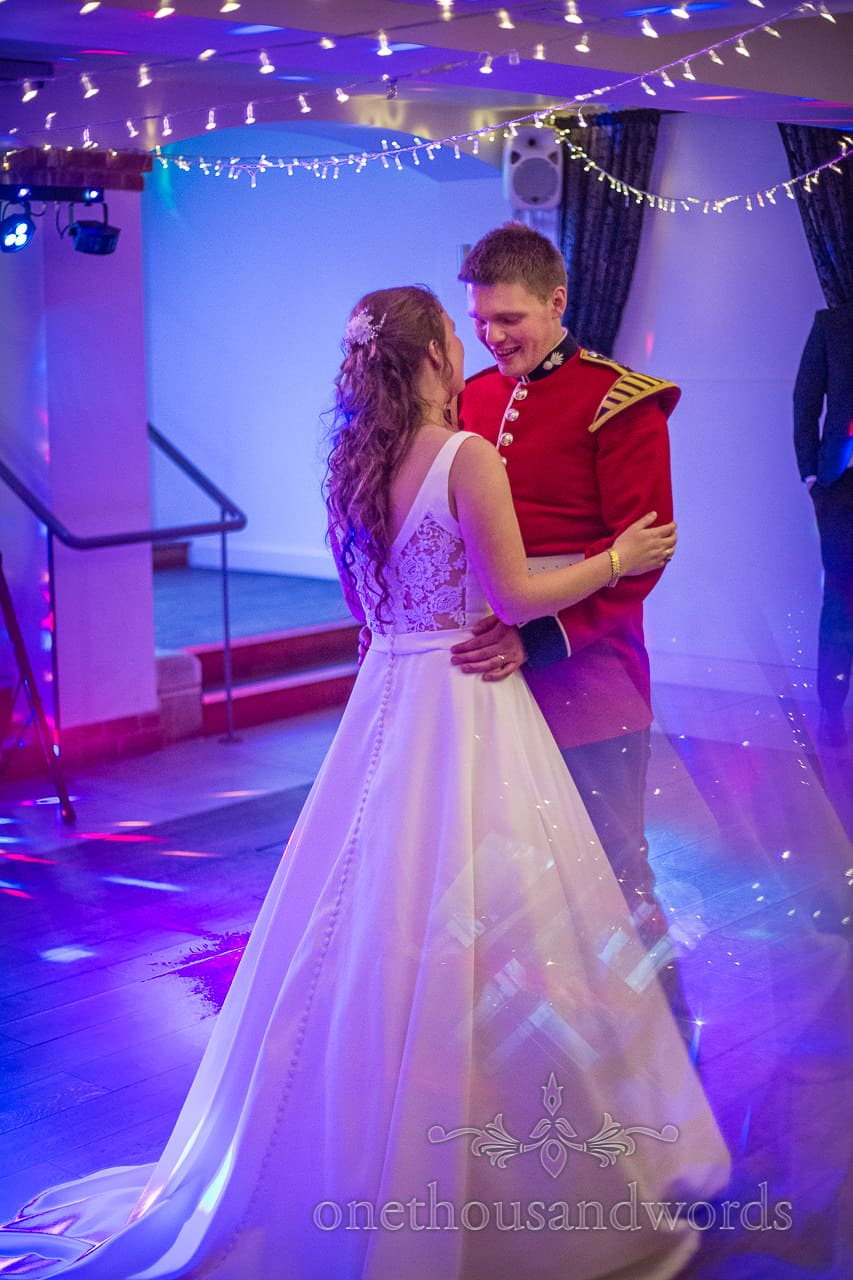 Military groom and bride in white wedding dress have Wedding First Dance under Blue Disco Lights and Fairy Lights