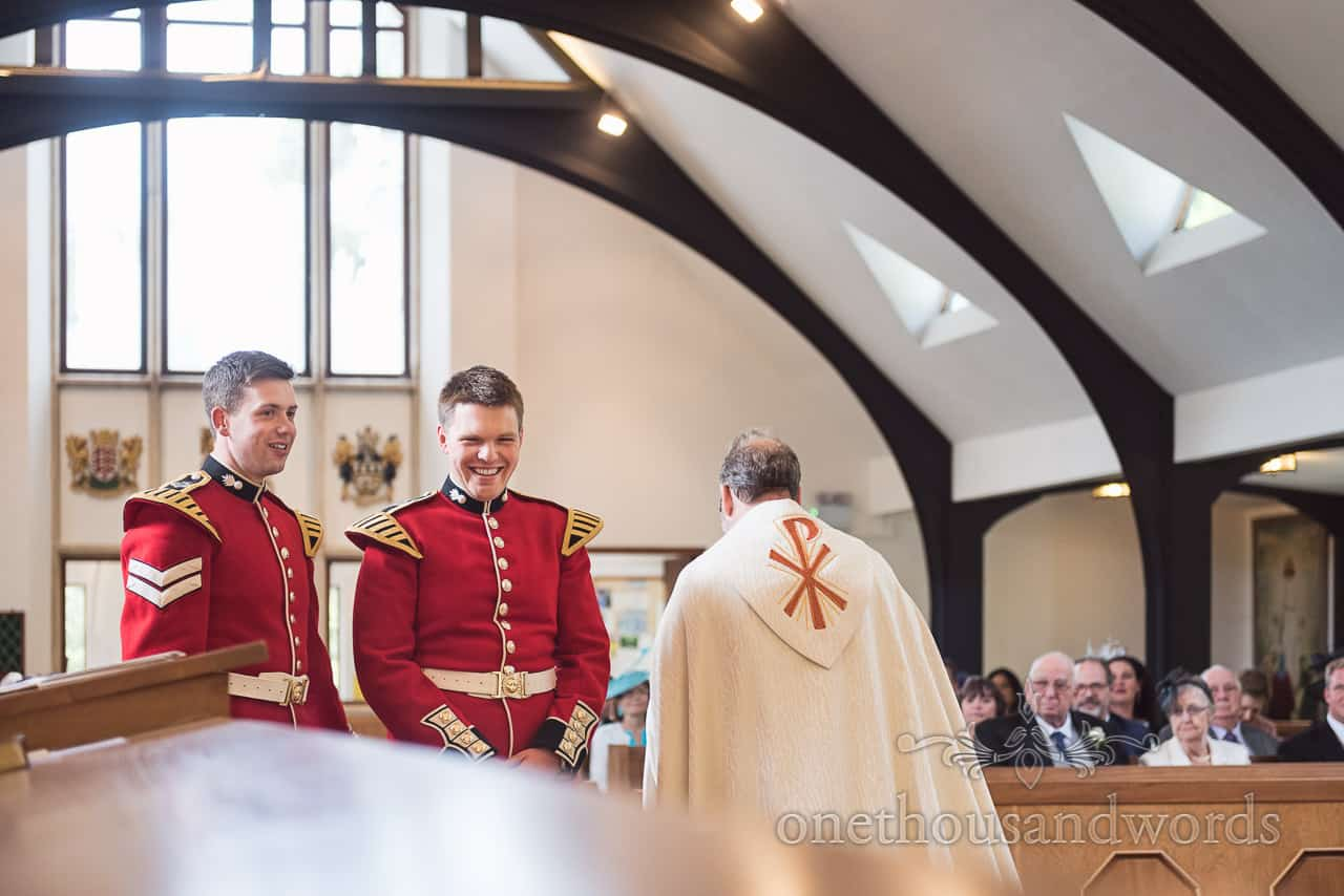 documentary photograph of Military Wedding Groom and Best Man in red uniforms Laughing before Church wedding Ceremony