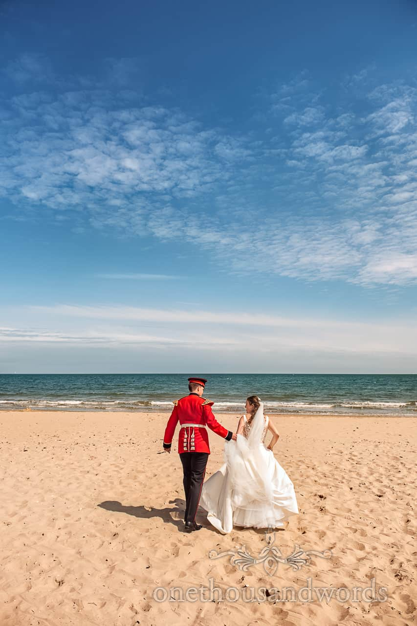Military groom in red uniform and bride in white Wedding dress Photograph of walk on Dorset Beach with sea and blue sky