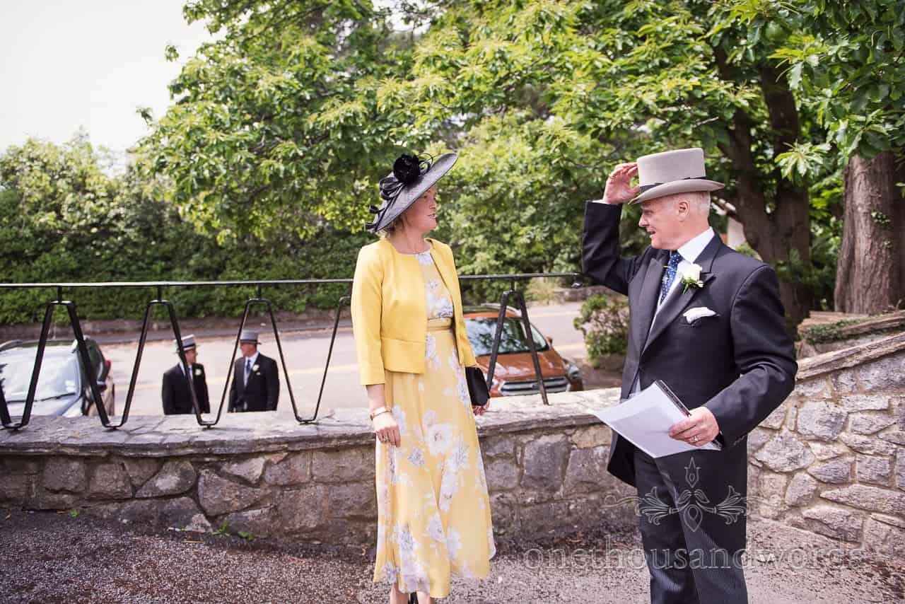 Mother of Bride in yellow Floral Dress talks to Father of Groom in Top Hat and Tails outside Sandbanks Church wedding venue