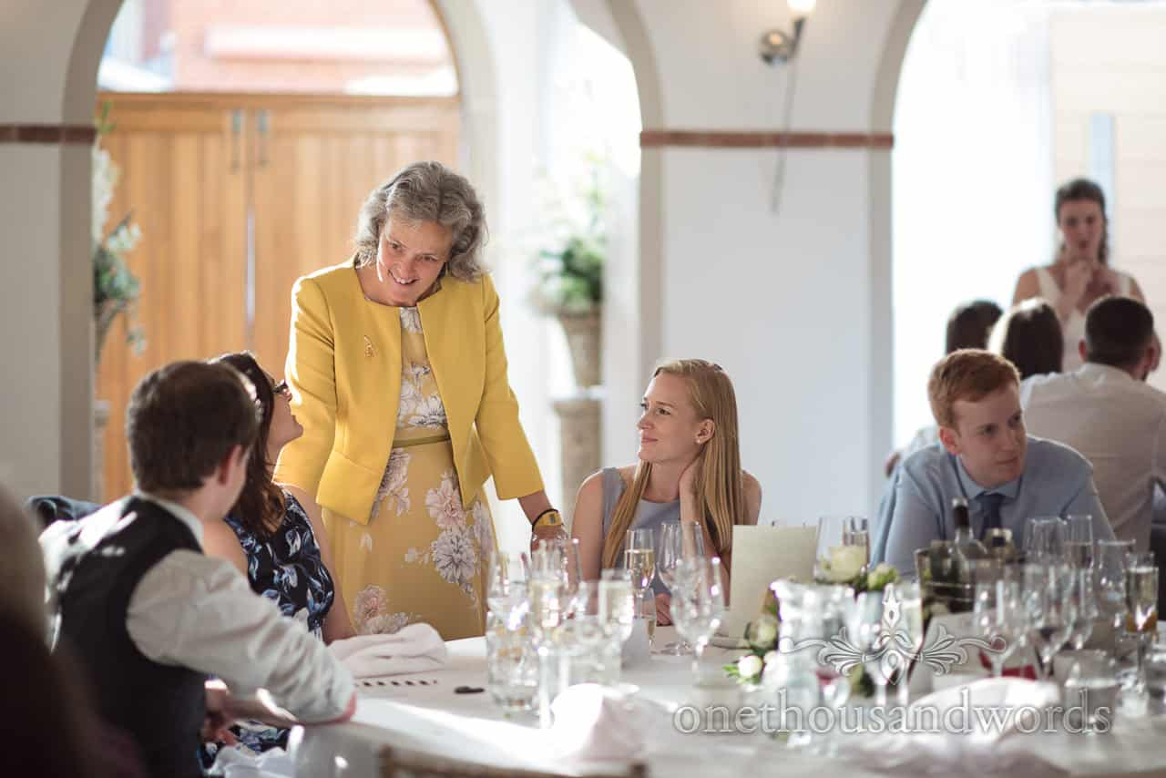 Mother of Bride in yellow dress Talks to Guests at Wedding Breakfast Tables at Italian Villa wedding venue