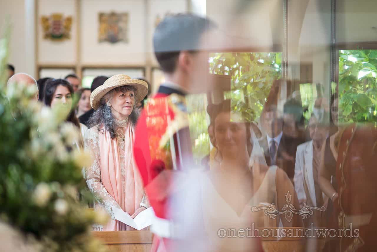 Mother of the Groom in hat Watches the Bride during Church Wedding Ceremony with reflection of brides face