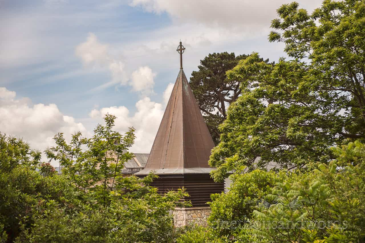 The Church Of Transfiguration Sandbanks Poole Church Wedding Venue Spire with blue summer sky and green Trees