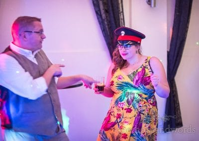 Wedding Guest in bright floral dress Wears Military Cap under disco lights during Wedding Evening Dancing Photographs