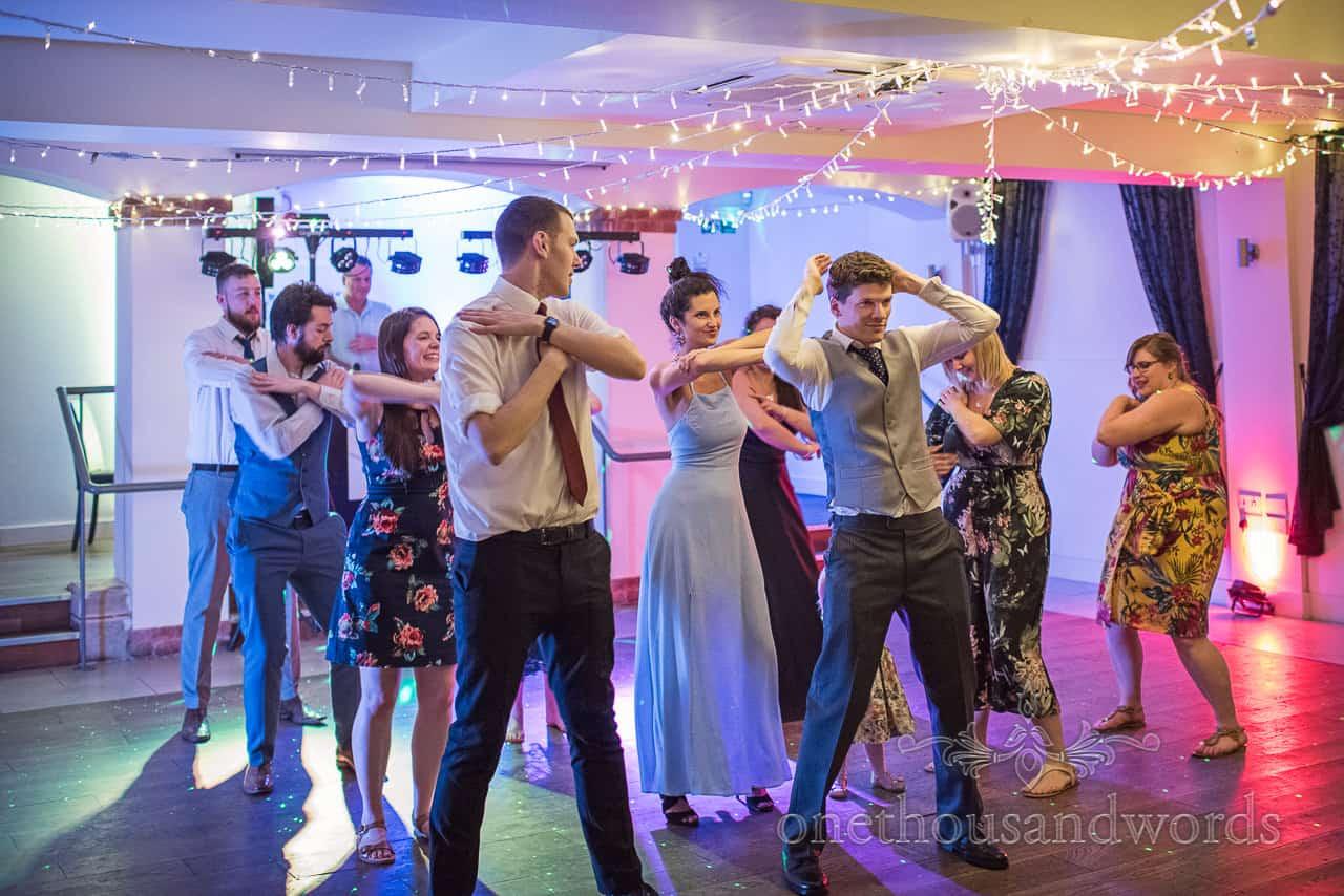 Wedding Guests Dance La Macarena together on wedding disco Dance Floor with coloured lights at The Italian Villa