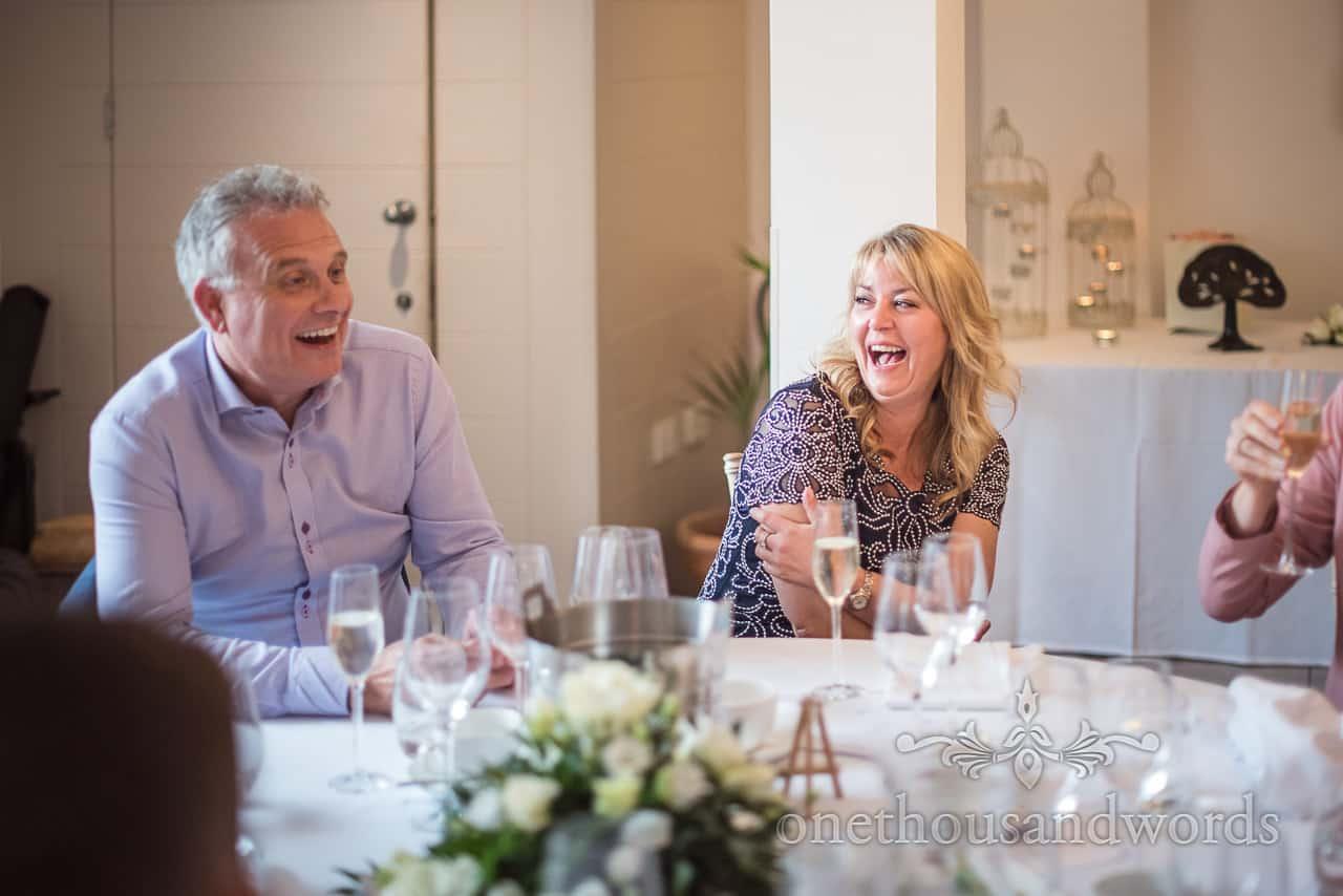 Wedding Guests Laughing at joke at Italian Villa Poole Wedding Venue wedding breakfast documentary photograph