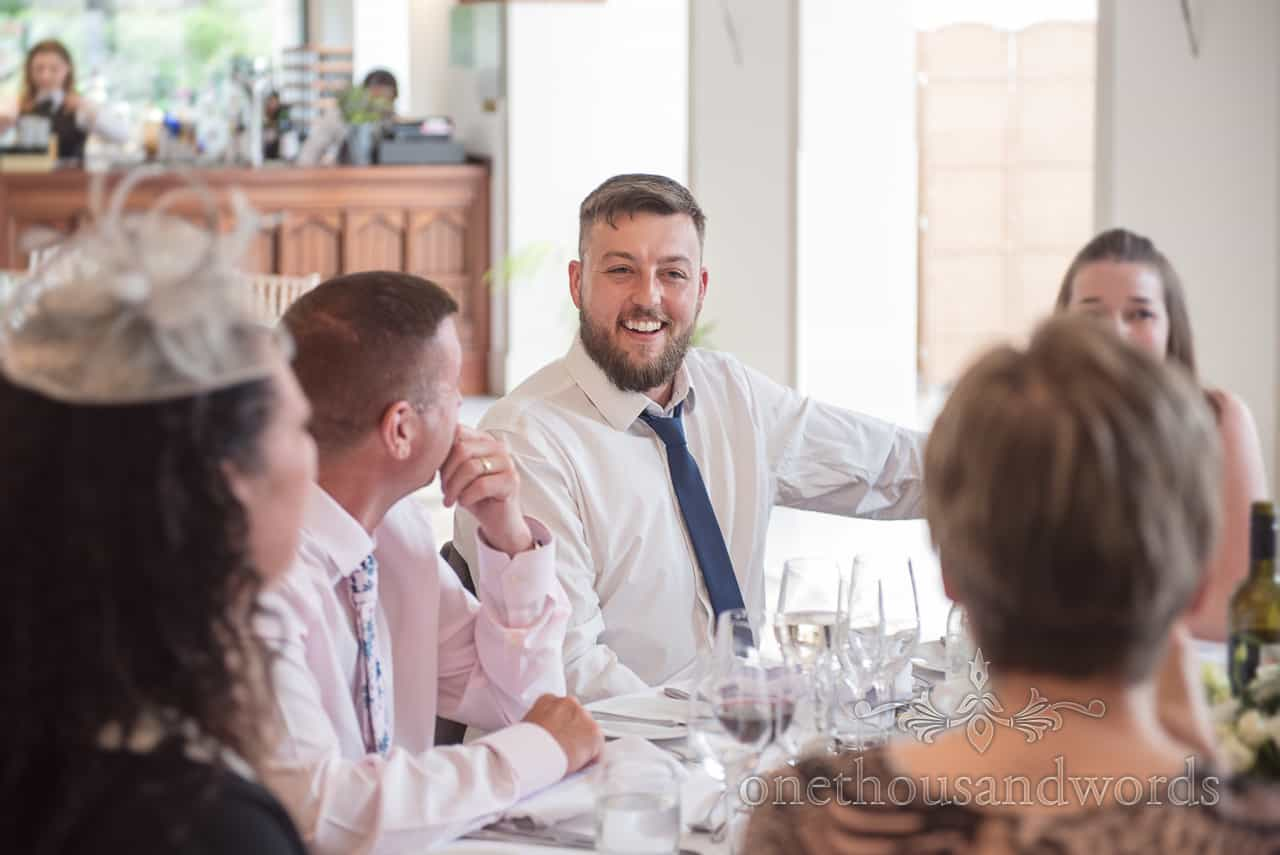 Wedding Guests sat at table Laughing together during Wedding Breakfast