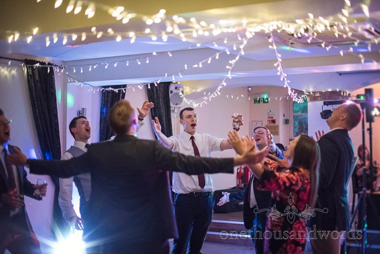 Wedding Guests Singing and Dancing together in a group circle under fairy lights at Evening Disco Photograph