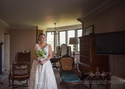 Bride in wedding dress with wedding bouquet at Studland Bay House in Bridal suite before wedding ceremony