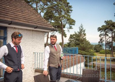 Groom and best man drink beer on coastal Knowl House Hotel balcony on summer wedding morning in Dorset
