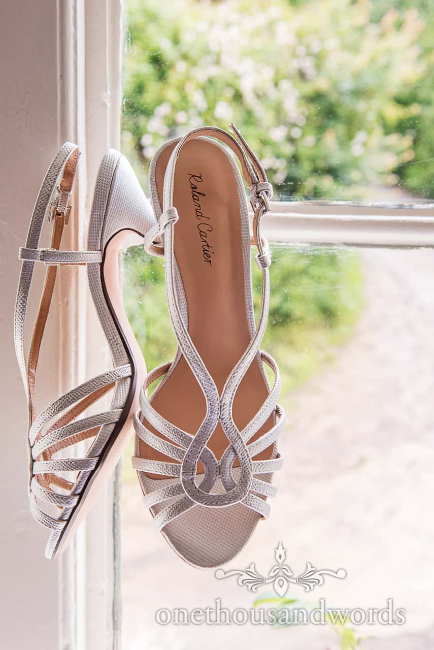 Sparkly silver two part diamante sandal Roland Cartier wedding shoes hanging in window on wedding morning