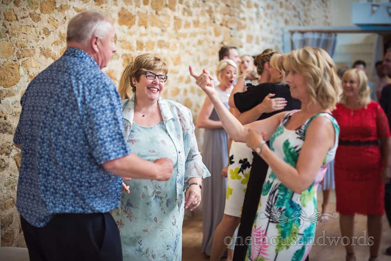 animated dancing guests having fun at Tithe Barn wedding evening reception in Dorset