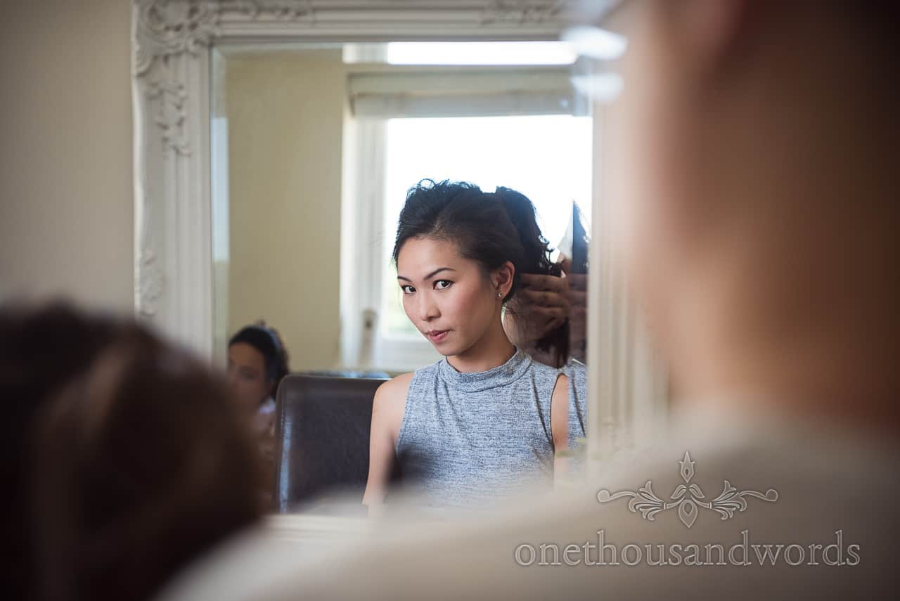 Reflection of Asian bridesmaid during hair styling in mirror