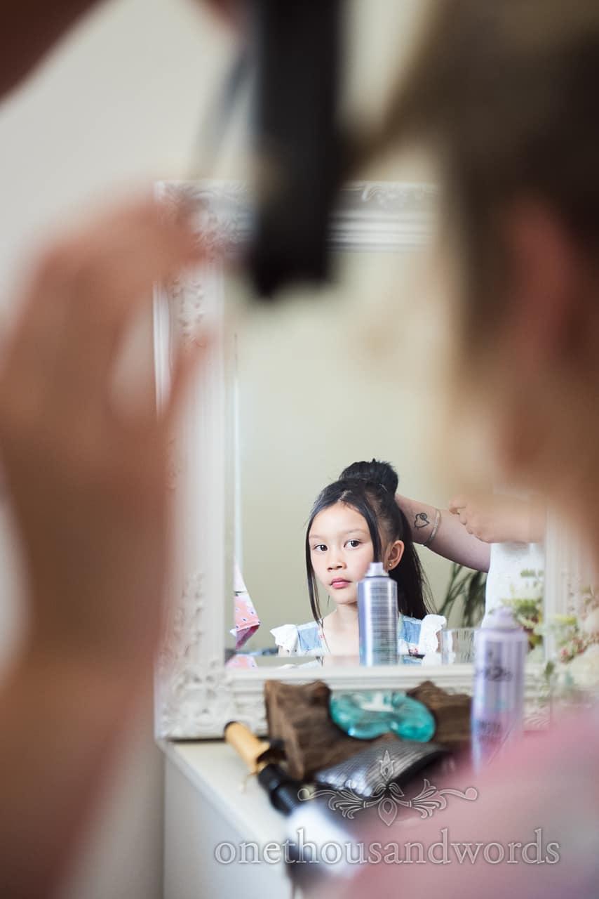 Asian bridesmaid has hair styled during morning preparations