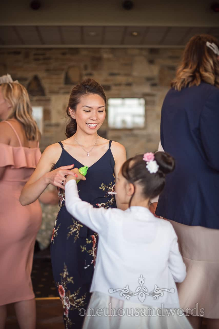 Asian wedding guest dancing with flower girl during Golf club reception