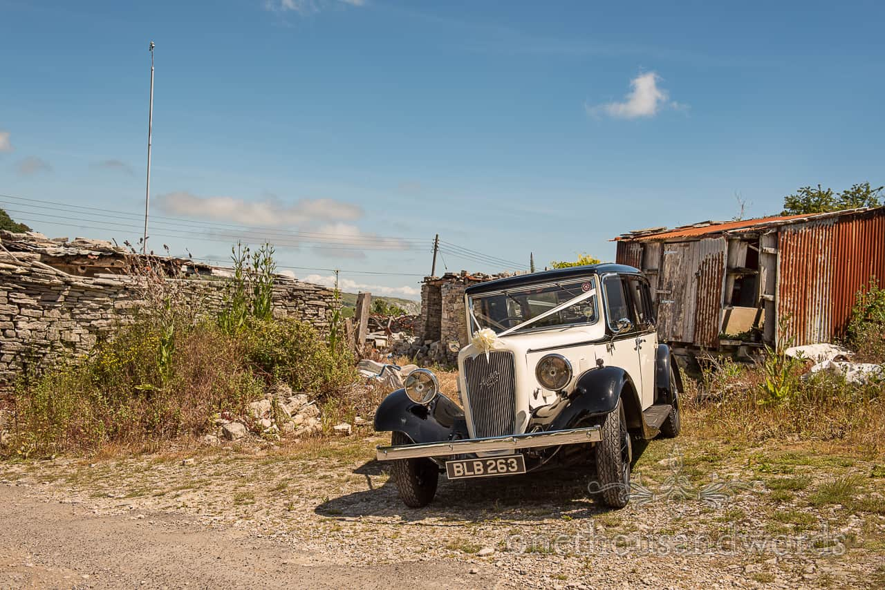Austin six classic wedding car parked by Dorset stone walls and rusty corrugated building