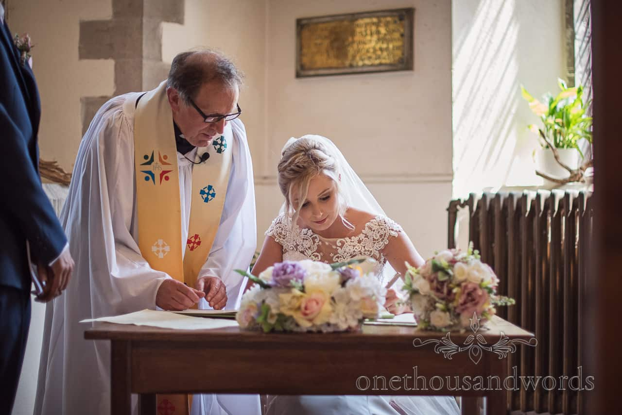 Beautiful blonde bride signs marriage register overseen by vicar in Dorset church