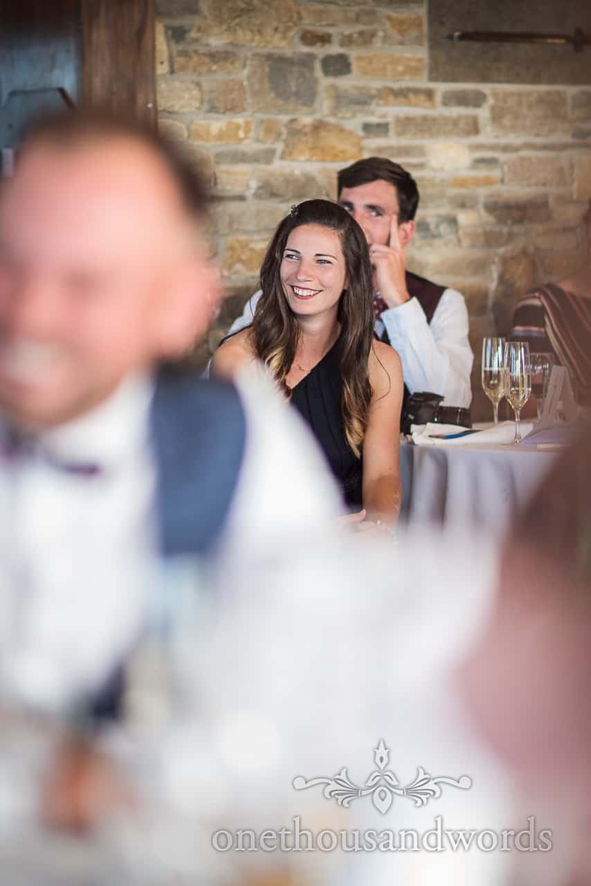 Beautiful female wedding guest laughs during wedding speeches at Isle of Purbeck Golf Club
