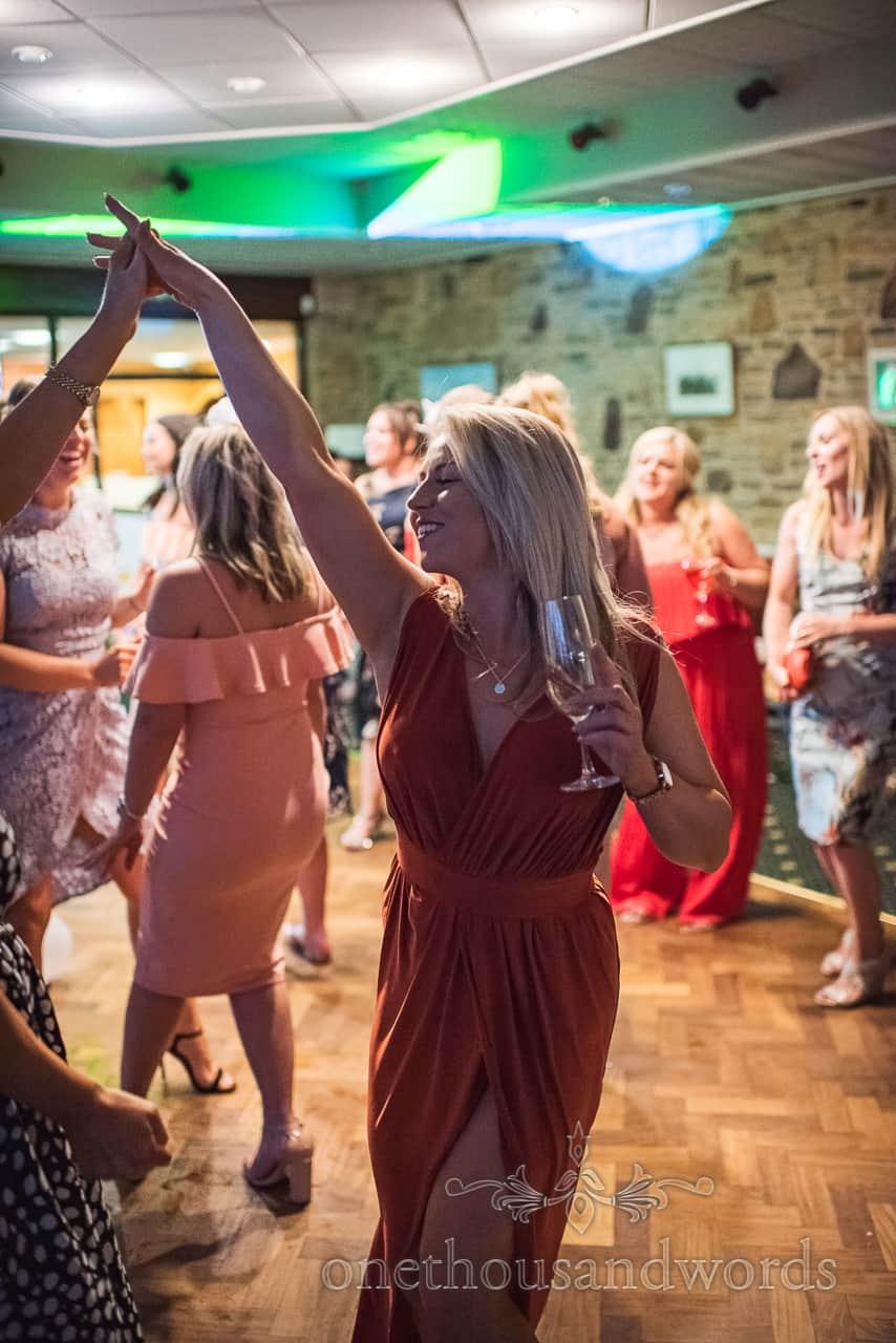 Beautiful wedding guest in orange dress dances at Golf Club wedding disco in Dorset