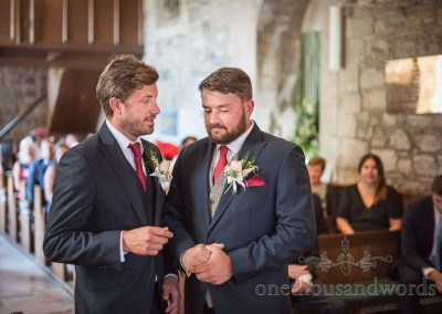 Documentary wedding photograph of best man giving groom a final pep talk before Dorset stone church wedding ceremony