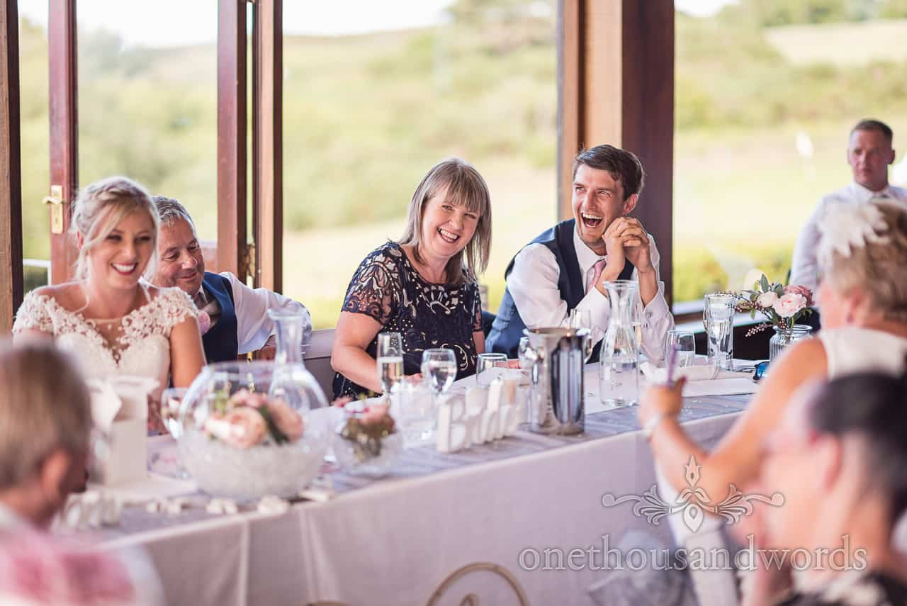Best man and parents laughing reaction to grooms wedding speech at Golf club reception