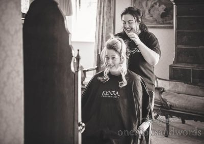 Black and white documentary photograph of bridal hair styling at Dorset wedding morning in Studland Bay House wedding venue