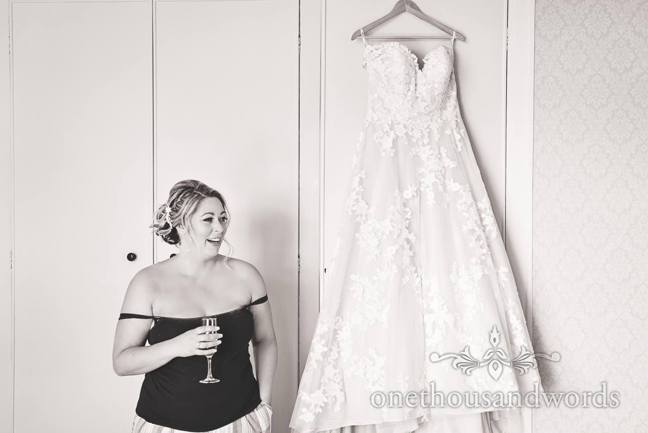 Black and white wedding photograph of wedding dress and bride with glass of bubbles on wedding morning