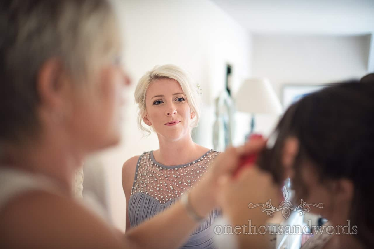 Smiling blonde bridesmaid in pastel blue dress looks on during bridal hair styling Dorset barn wedding