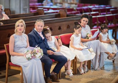Flower girl and father of bride cuddle during church wedding ceremony in Swanage, Dorset