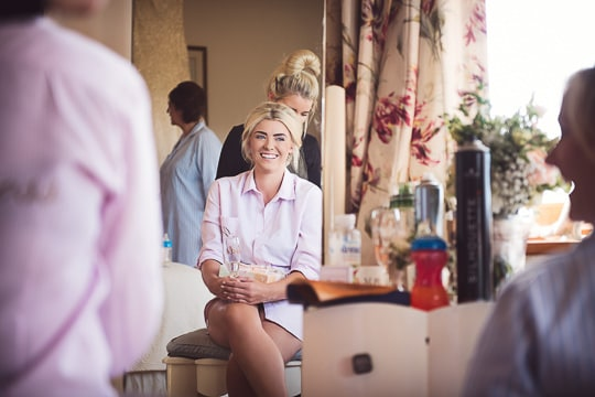 Bride has hair styled during bridal preparations in Dorset whilst groom is photographed elsewhere