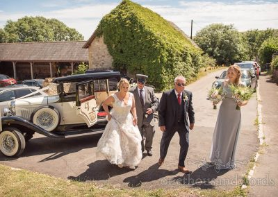 Bride father of bride and bridesmaid arrives in classic wedding car at Purbeck stone village wedding in Dorset