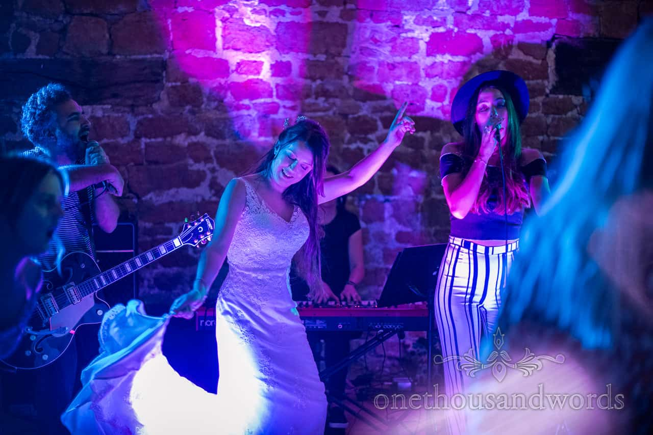 Happy bride dances with wedding band singer in blue and purple lights at Tithe Barn Dorset