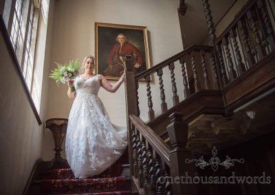 Bride descends ornate wooden staircase at Studland Bay House Dorset wedding venue photograph