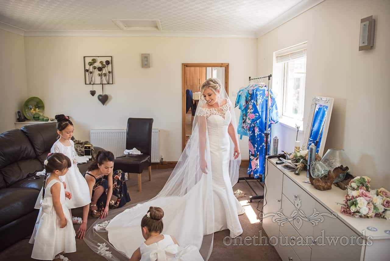 Brides dress train adjusted by flower girls at family home on Dorset wedding morning