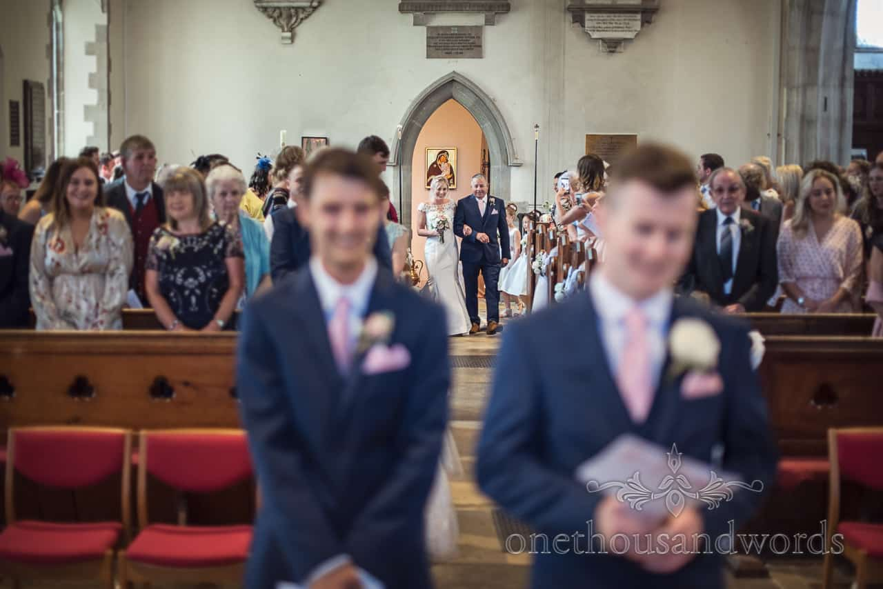 Bride and father arrive at back of church aisle at St Mary's church wedding ceremony in Swanage