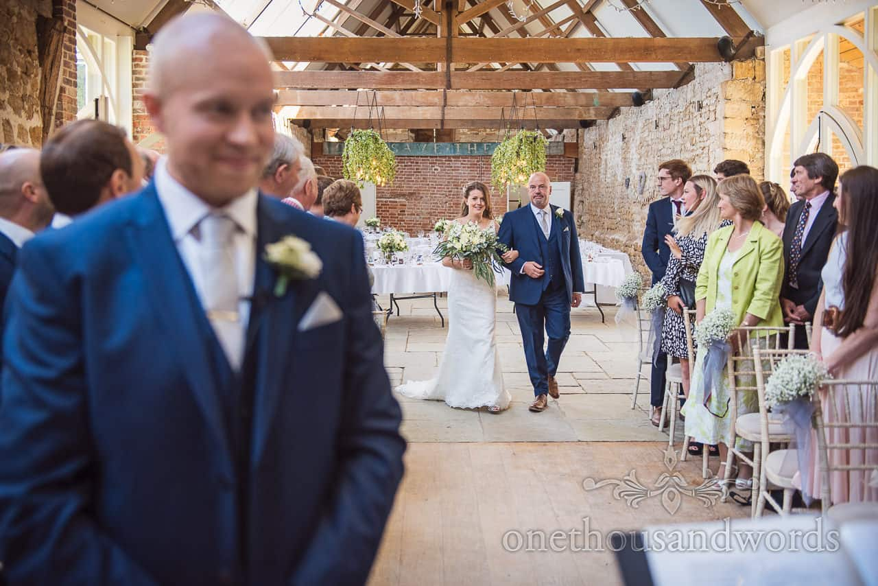 Smiling bride and father coming down aisle while groom waits at Tithe Barn Dorset wedding