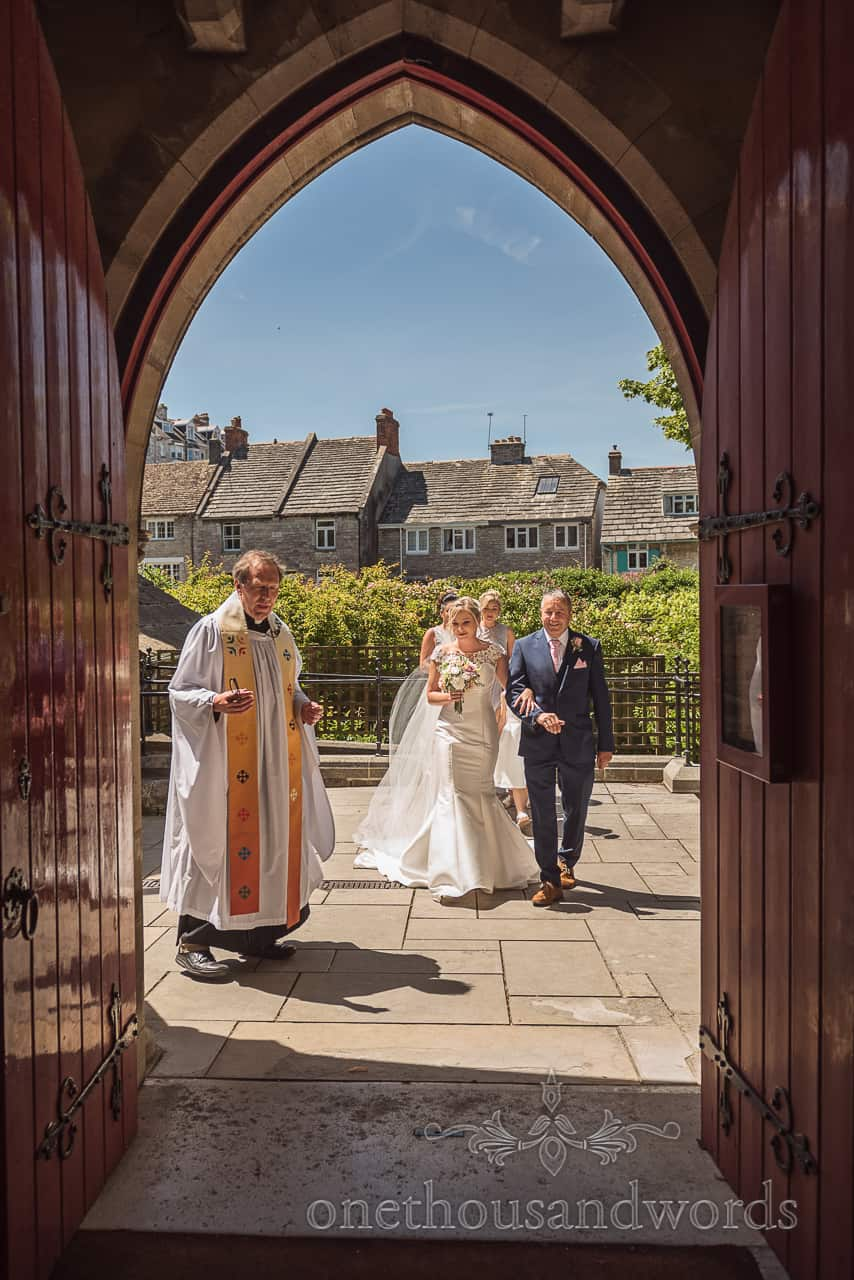 Bride, father and vicar entering church doorway before wedding ceremony in Swanage