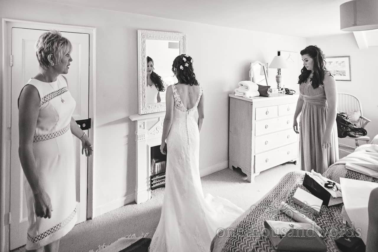 Bride in dress checks herself in mirror at Symondsbury Estate cottage Dorset wedding morning
