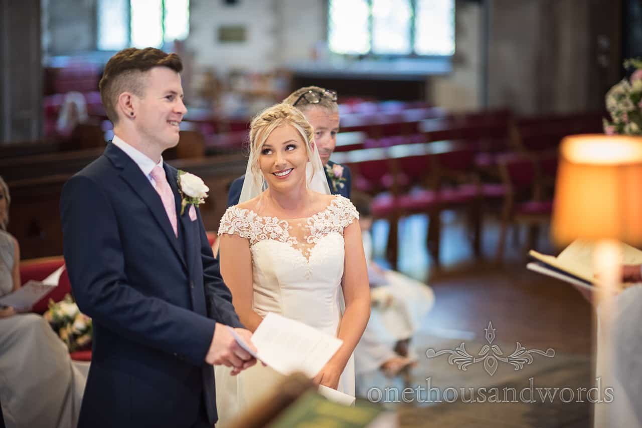 Bride gives groom funny look during English church wedding ceremony in Swanage