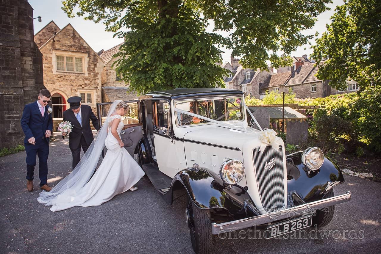 Bride and groom boarding Austin Six classic wedding car transport at church wedding venue in Dorset