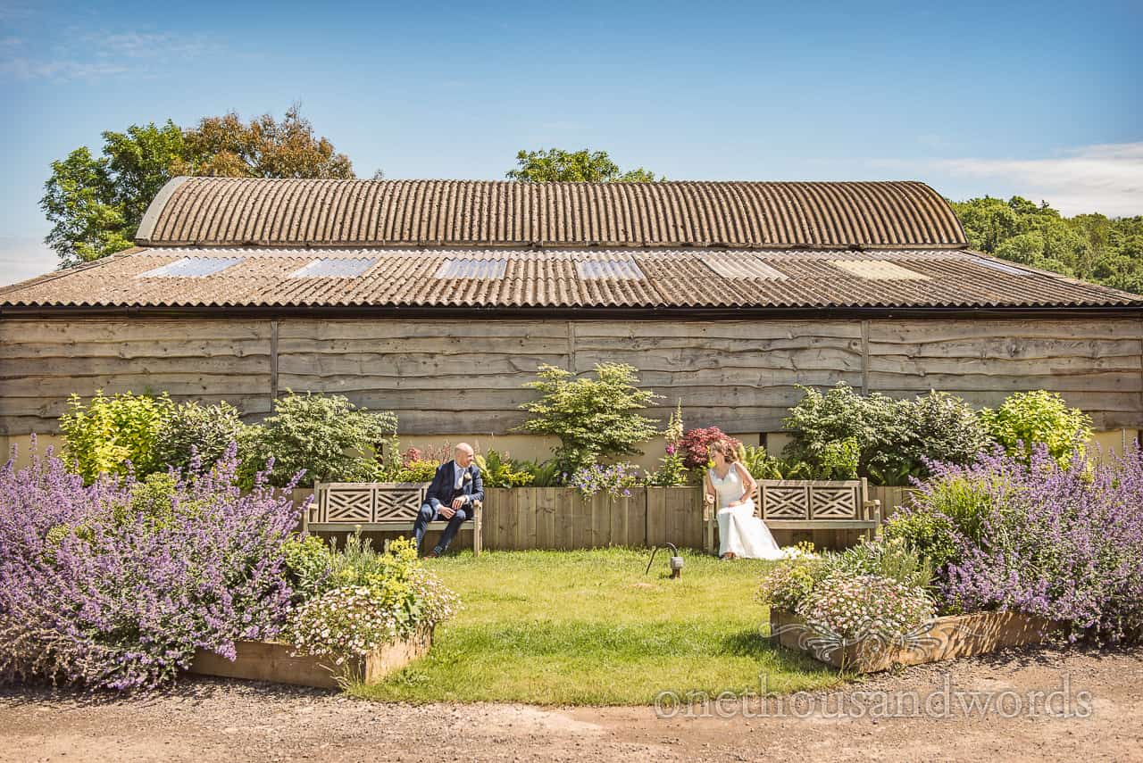 Bride and groom sitting on benches in front of barn at the Tithe Barn Dorset wedding