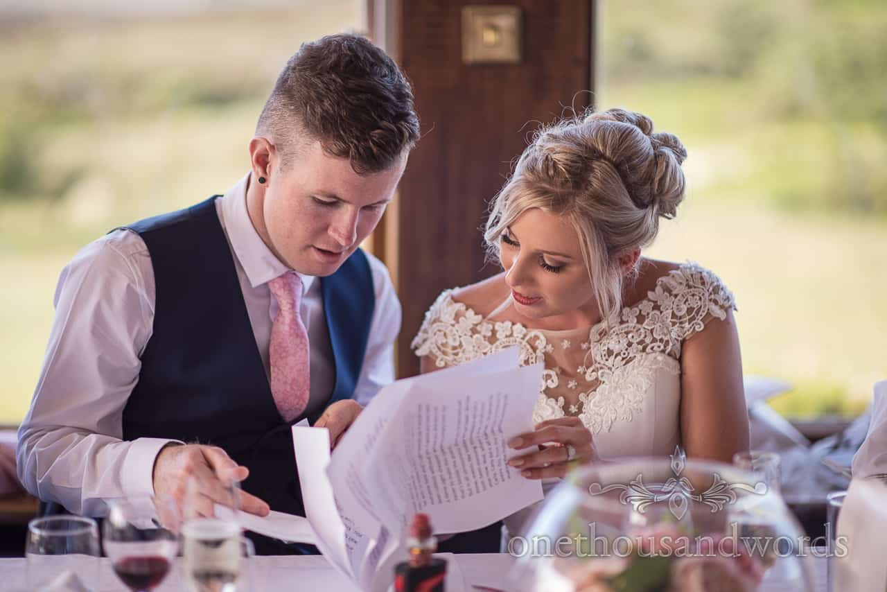 Bride and groom check over wedding speech while sat at top table at Golf club reception