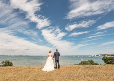 Bride and groom with Dorset coastal landscape and blue sky wedding photograph at Studland Bay House wedding venue