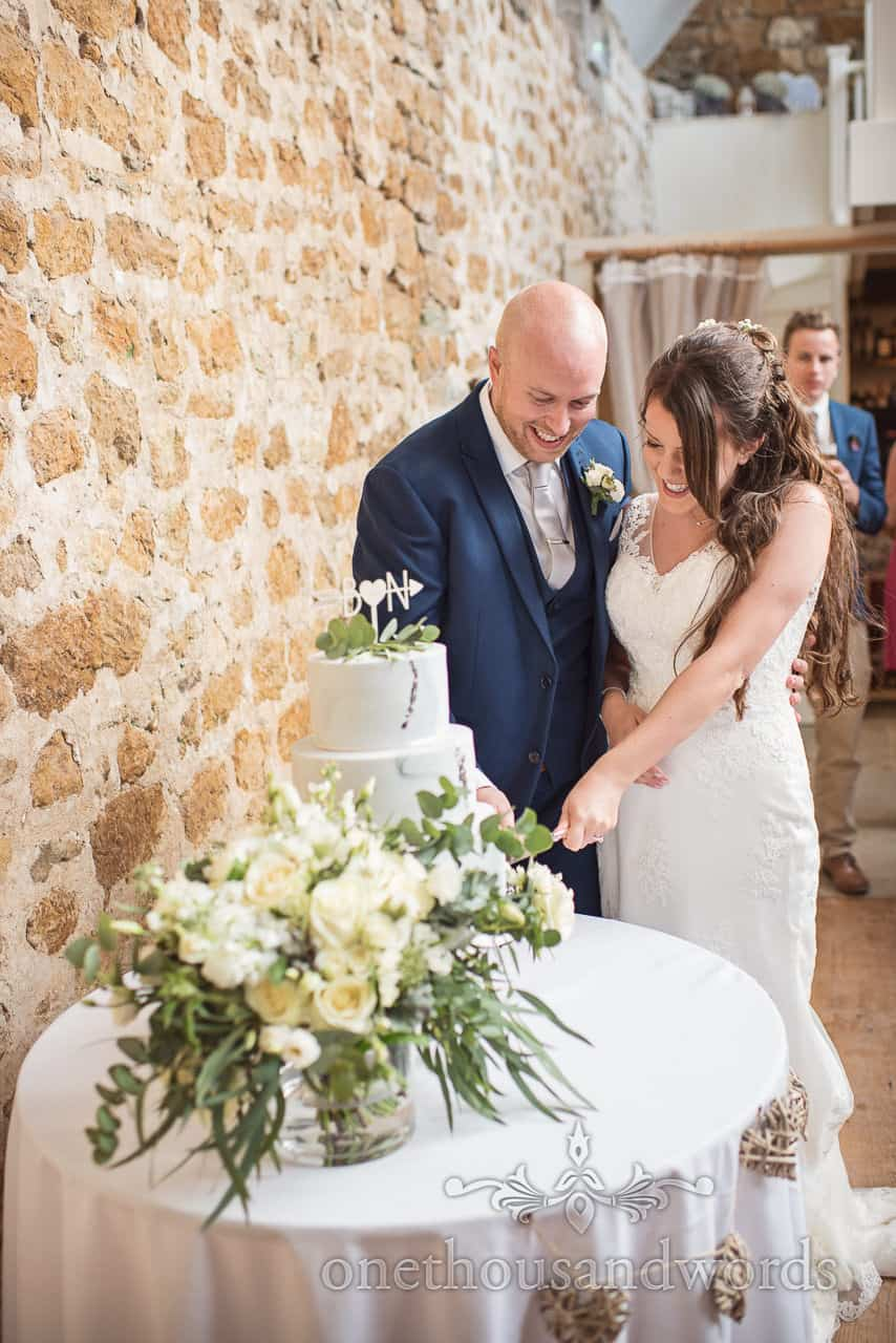 Photograph of bride and groom cutting the wedding cake at Tithe Barn Symondsbury wedding venue in Dorset