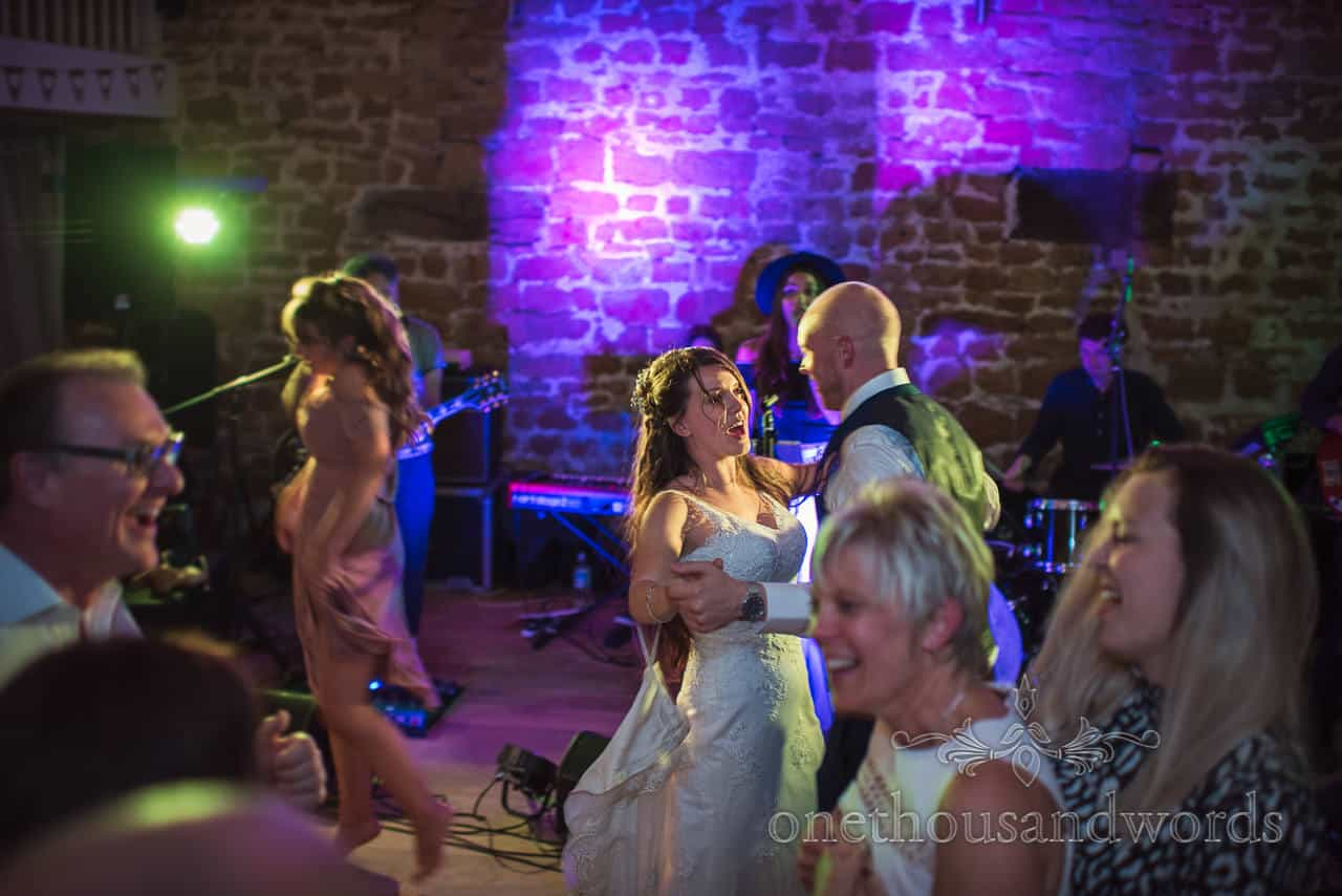 Photograph of bride and groom dance to wedding band among wedding guests at the Tithe Barn evening disco