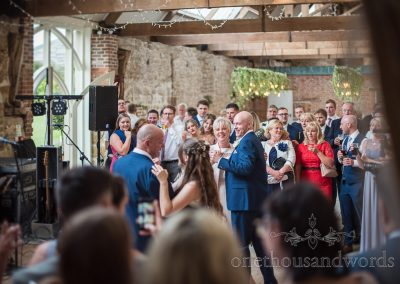 Bride and groom dance with their parents during evening reception as guests look on at the Tithe Barn