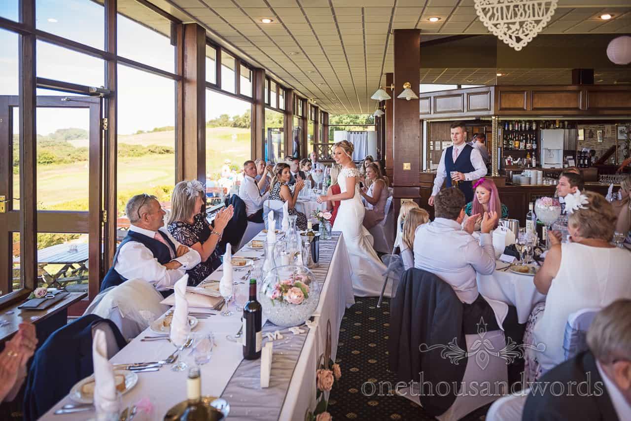 Guests applaud as bride and groom enter Purbeck golf club wedding breakfast