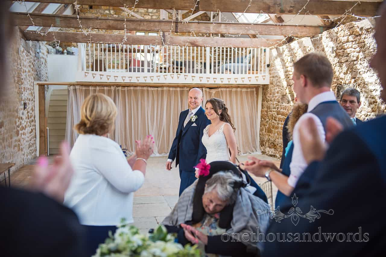 Bride and groom enter the Tithe Barn wedding breakfast to standing ovation from guests