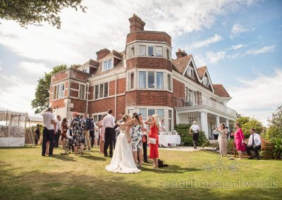 Bride hugged by wedding guest at garden drinks reception at Studland Bay Dorset wedding photograph